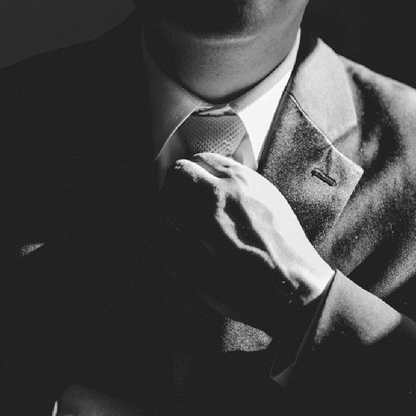 A man tightening his tie with a high contrast light on his shoulder