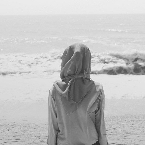 A young person in a shawl staring out into the ocean