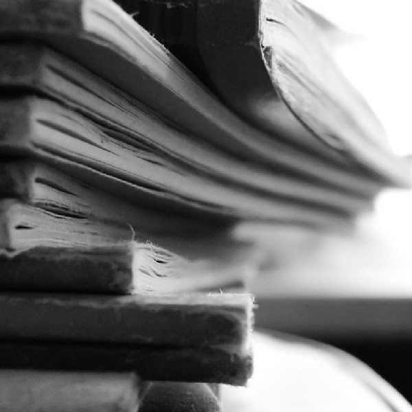 A close up of old books and papers stacked together