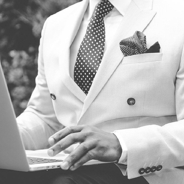 A man in a white tuxedo sitting with a macbook