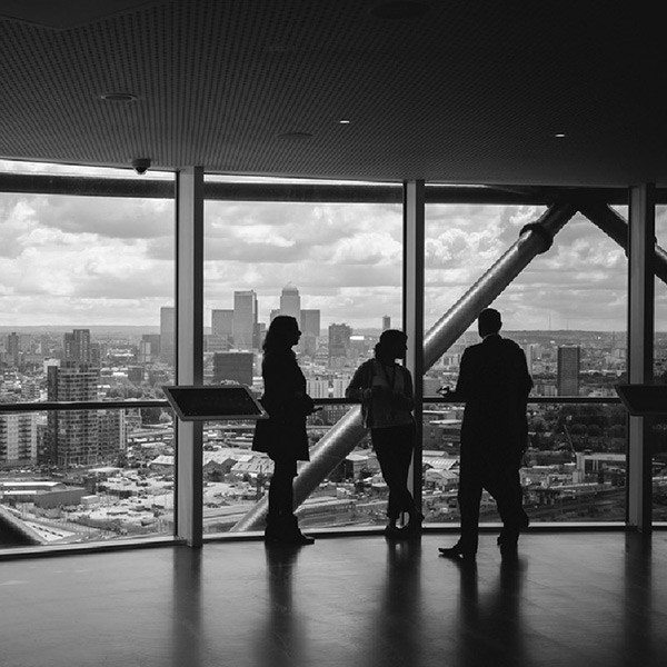 3 people standing by a large window in a tall skyscraper overlooking a cityscape