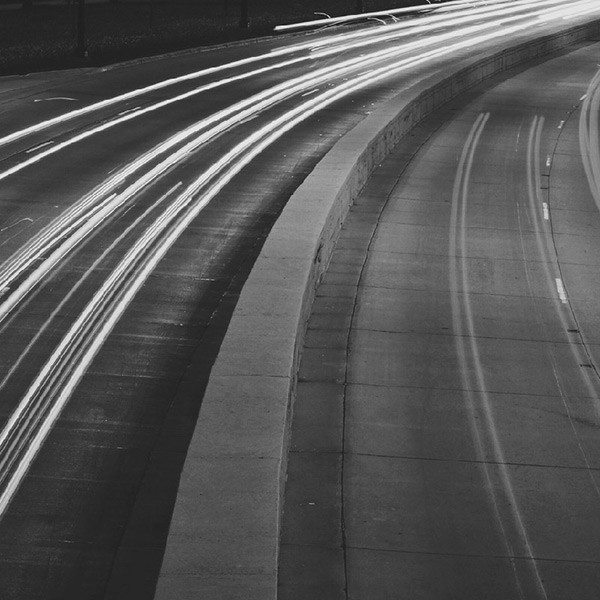 A long exposed shot of cars on a highway creating a blur of lights and streaks.
