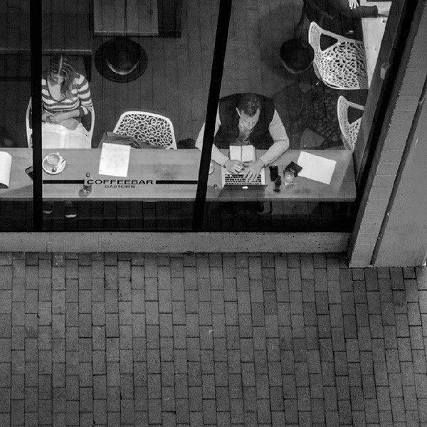 Looking down on a couple in a cafe on their computers and drinking coffee